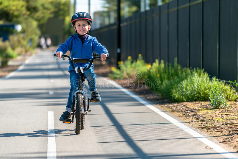 Menino feliz que monta sua bicicleta na pista da bicicleta imagens de stock royalty free