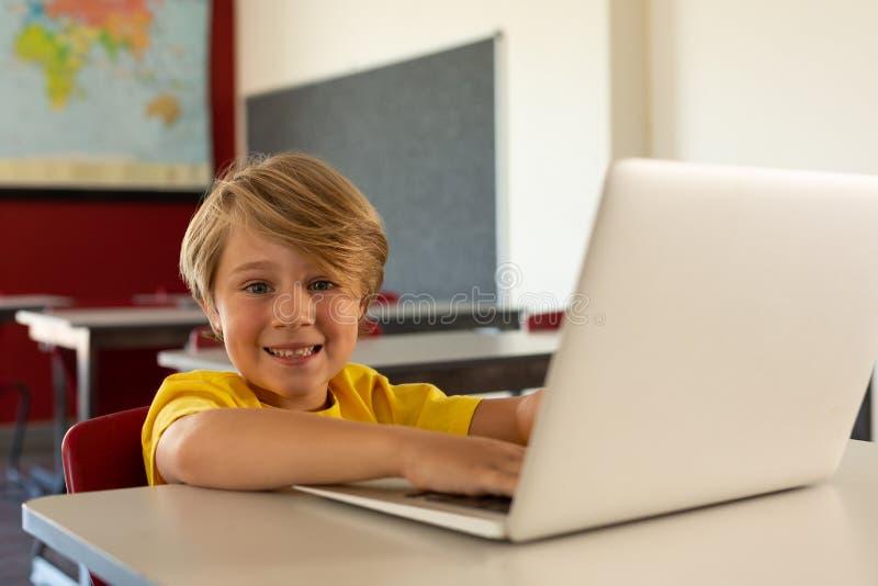 Menino feliz que olha a câmera ao usar o portátil na mesa em uma sala de aula fotos de stock