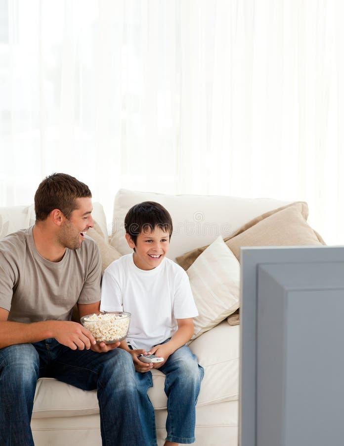 Menino feliz que presta atenção à tevê com seu pai foto de stock