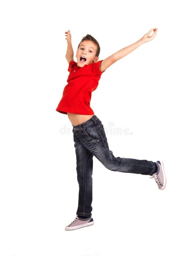 Menino feliz que salta com mãos levantadas acima fotos de stock