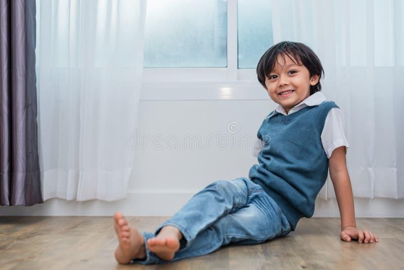 Menino feliz que senta-se e que sorri no quarto Conceito dos estilos de vida e dos povos Conceito da vida do retrato e da felicid imagem de stock