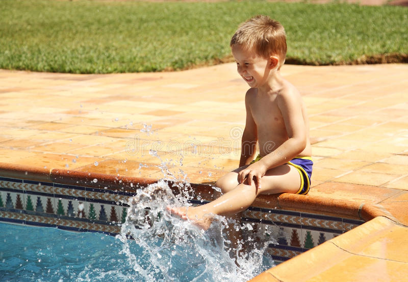 Menino feliz que tem o divertimento na piscina fotos de stock royalty free