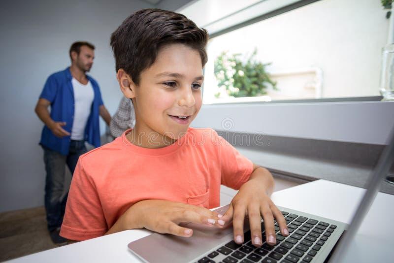 Menino feliz que usa o portátil imagem de stock