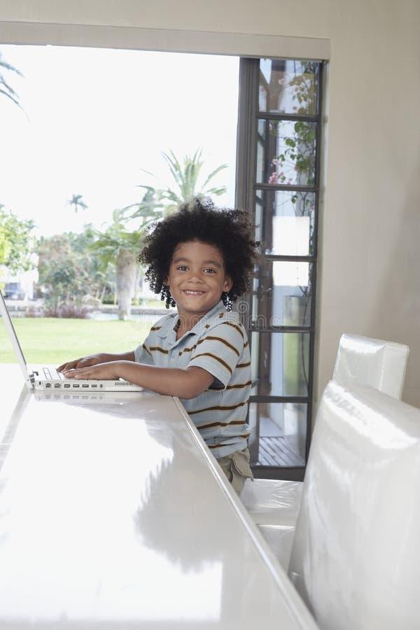 Menino feliz que usa o portátil na mesa de jantar fotografia de stock royalty free