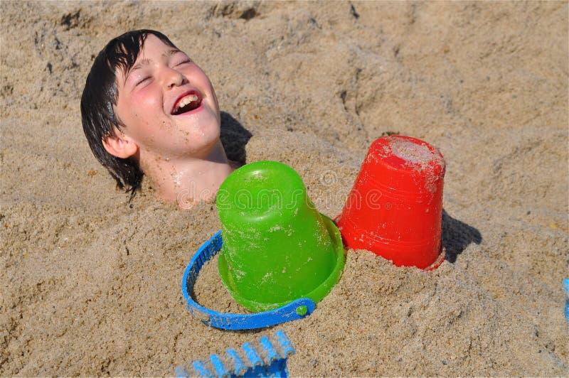 Menino feliz sob a areia fotografia de stock royalty free