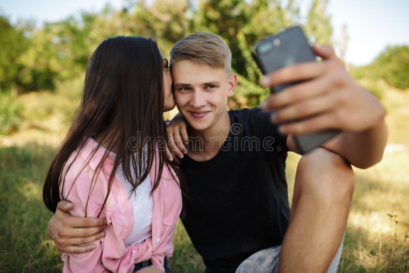 Menino fresco novo que senta-se no gramado no parque e que abraça a menina ao fazer o selfie foto de stock royalty free