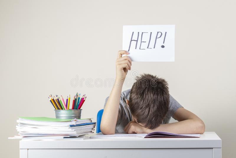 Menino frustrante cansado triste que senta-se na tabela com muitos livros e que guarda o papel com ajuda da palavra Dificuldades  foto de stock royalty free