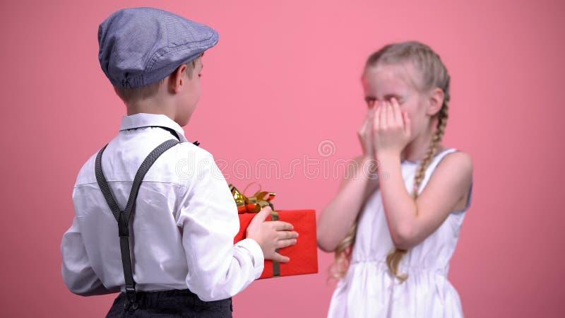 Menino galhardo surpreendente sua amiga pequena com presente, celebração do aniversário imagens de stock royalty free