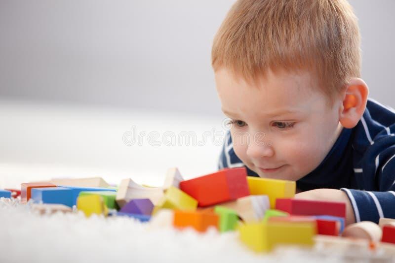 Menino gengibre-de cabelo adorável que joga com cubos imagens de stock