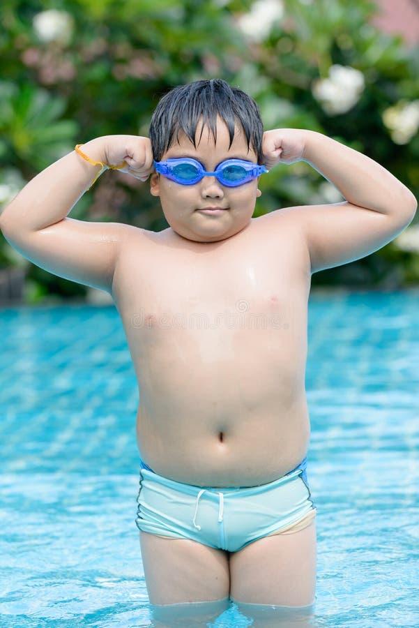 Menino gordo asiático que mostra lhe o músculo fotografia de stock