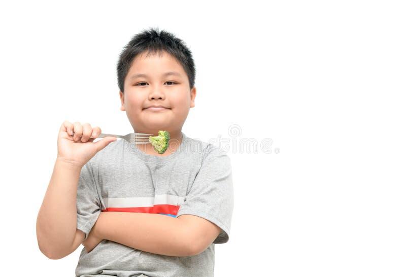 Menino gordo obeso com os brócolis disponível isolados foto de stock