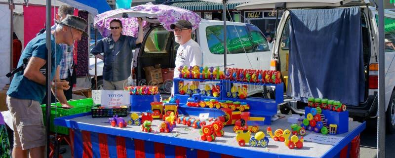 Menino grande encantado pelos brinquedos de madeira pintados em uma tenda do mercado de Nelson foto de stock royalty free