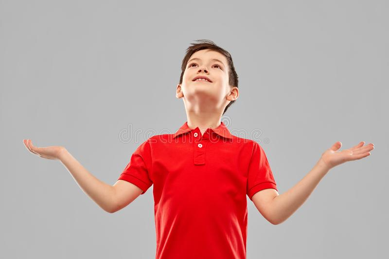 Menino grato feliz no t-shirt vermelho que olha acima imagem de stock royalty free