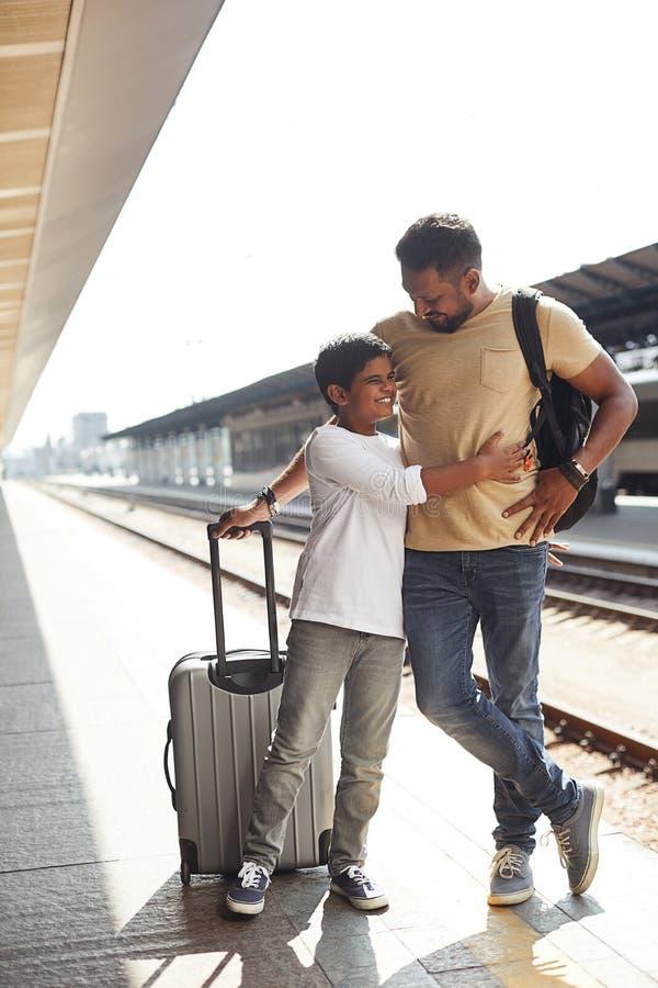 Menino hindu alegre que abraça seu pai loving foto de stock