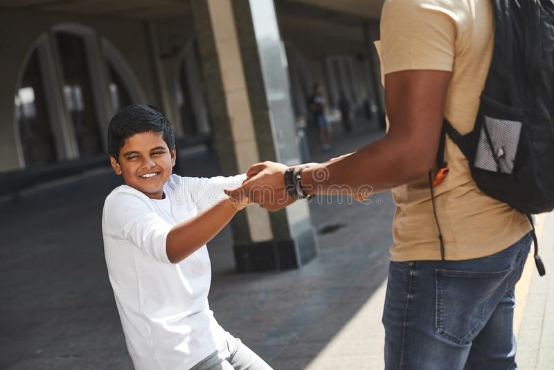 Menino hindu de sorriso que guarda suas mãos dos pais foto de stock