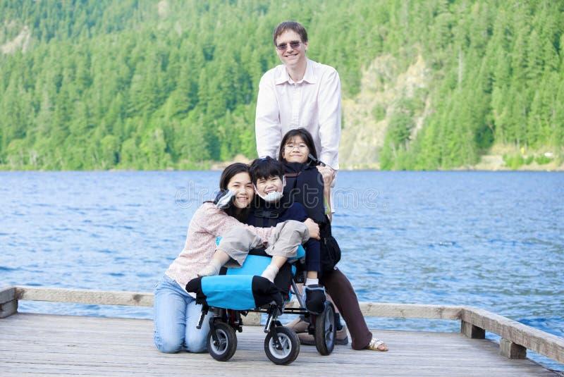 Menino incapacitado na cadeira de rodas cercada pela família imagem de stock royalty free