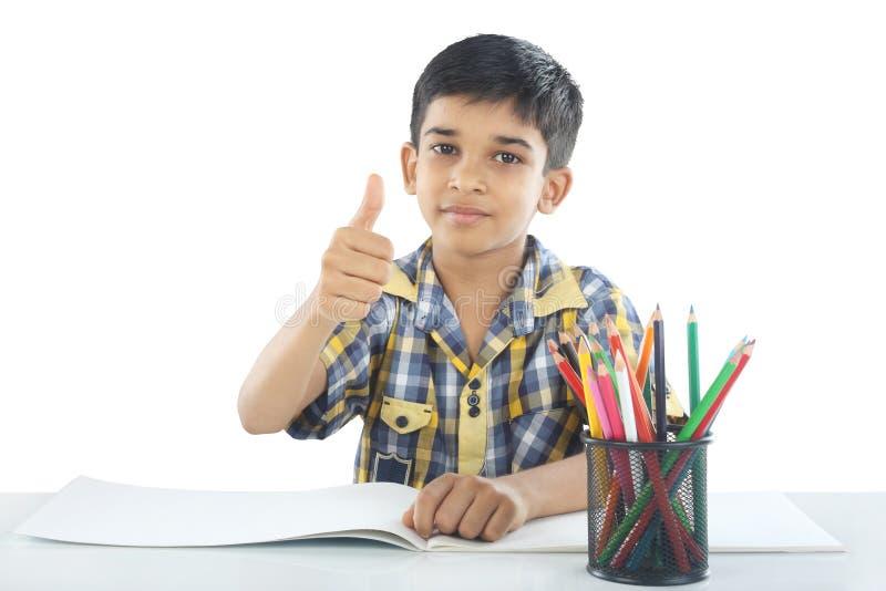 Menino indiano com nota e lápis do desenho imagem de stock