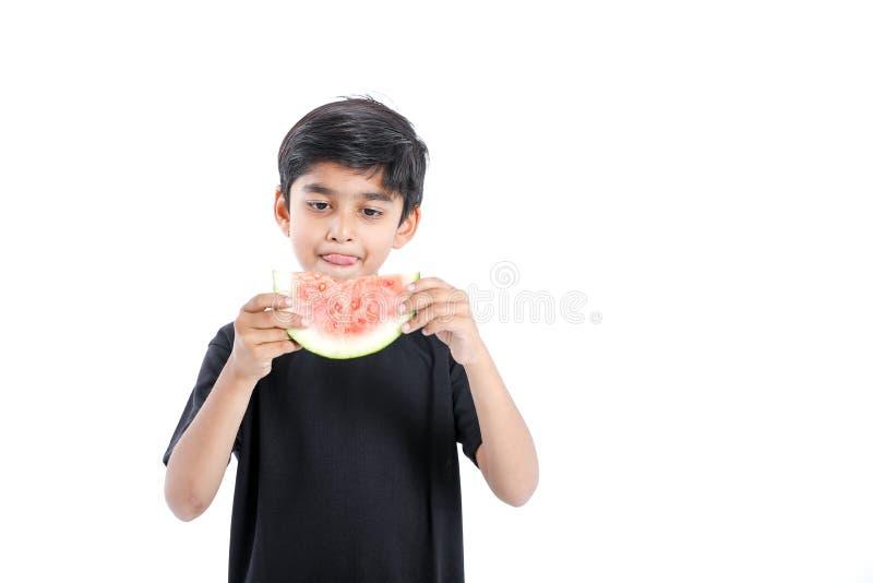 menino indiano pequeno que come a melancia com expressões múltiplas imagens de stock