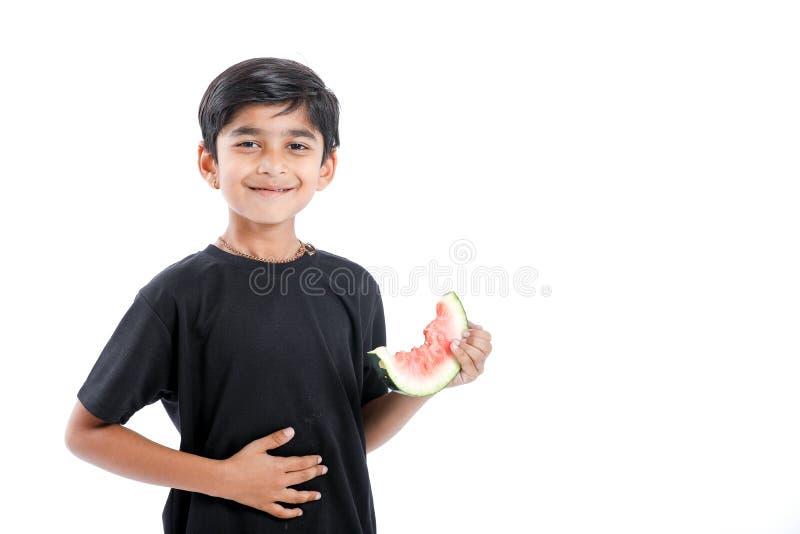 menino indiano pequeno que come a melancia com expressões múltiplas fotos de stock royalty free