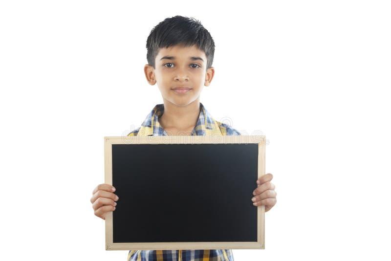 Menino indiano que guarda a ardósia da escola imagem de stock royalty free
