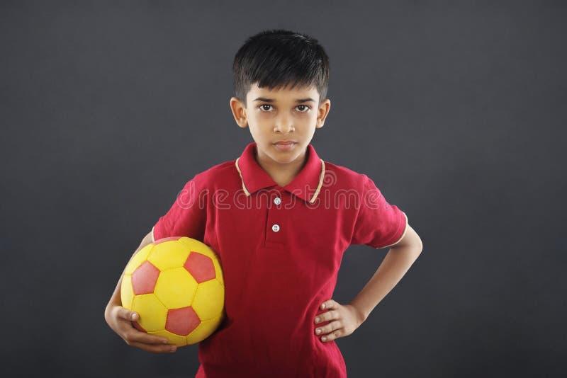 Menino indiano que guarda o futebol imagens de stock royalty free