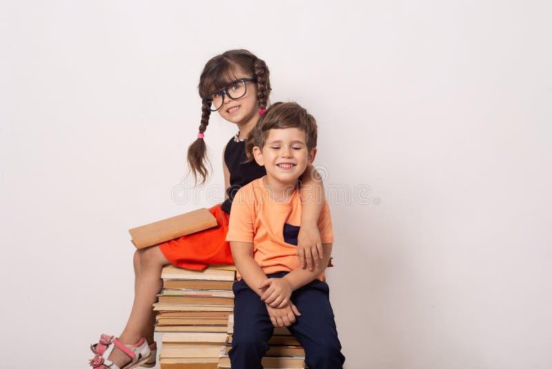 Menino industrioso e menina da criança com livros De volta ao fundo criativo da escola com alunos fotografia de stock royalty free