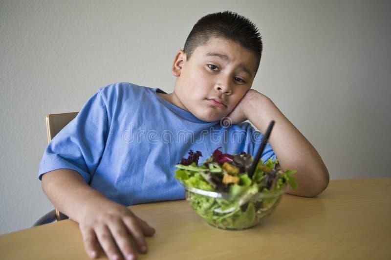 Menino infeliz do preadolescent que senta-se na mesa com salada fotos de stock royalty free