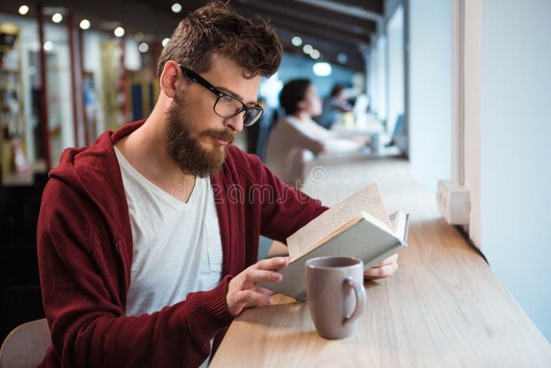 Menino inteligente no livro de leitura dos vidros que senta-se na mesa imagem de stock