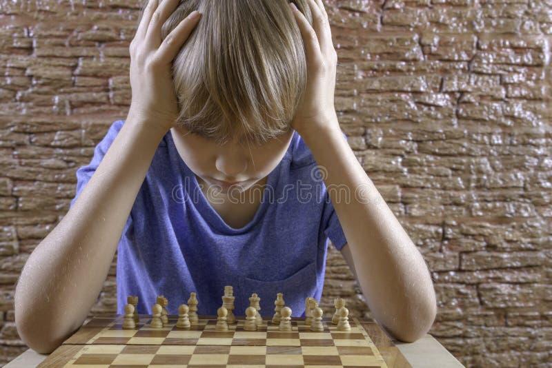 Menino inteligente sério que olha a placa de xadrez imagem de stock royalty free