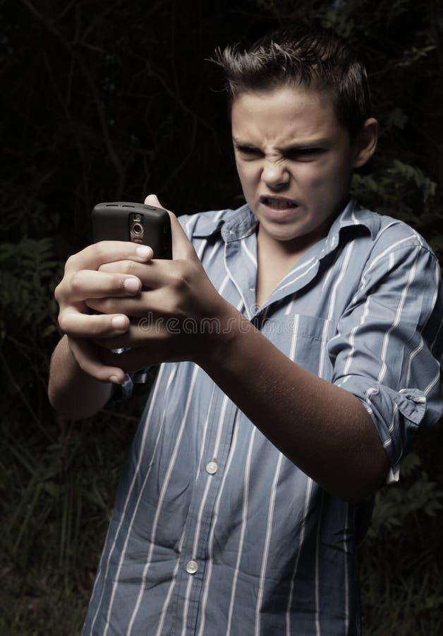 Menino irritado em seu telemóvel imagem de stock