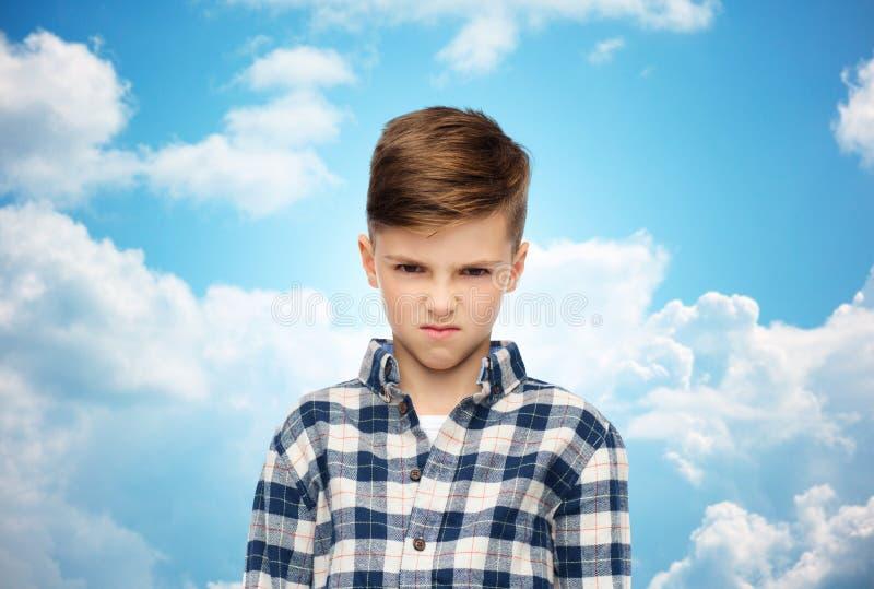 Menino irritado na camisa quadriculado sobre o céu azul fotografia de stock