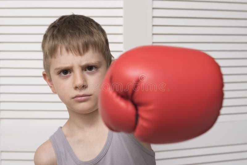 Menino irritado na luva de encaixotamento vermelha batida fotografia de stock royalty free