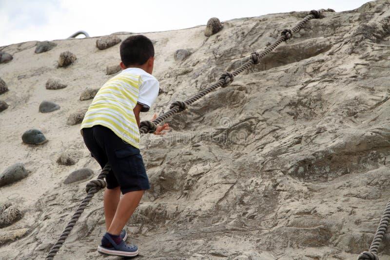 Menino japonês que escala na parede fotografia de stock