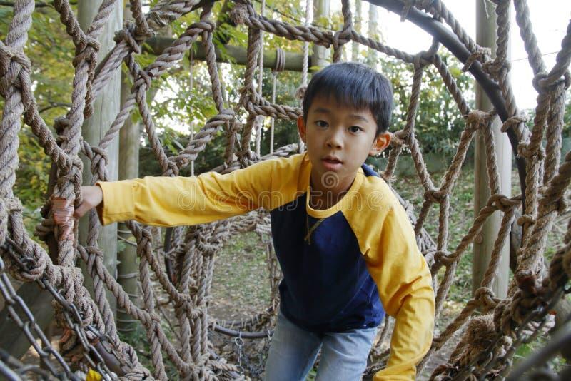 Menino japonês que joga no curso de obstáculo exterior foto de stock royalty free