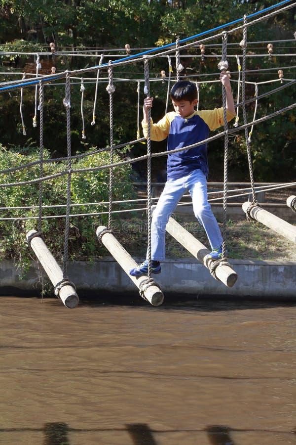 Menino japonês que joga no curso de obstáculo exterior fotografia de stock