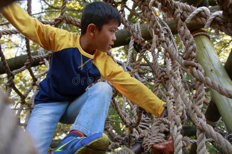 Menino japonês que joga no curso de obstáculo exterior foto de stock