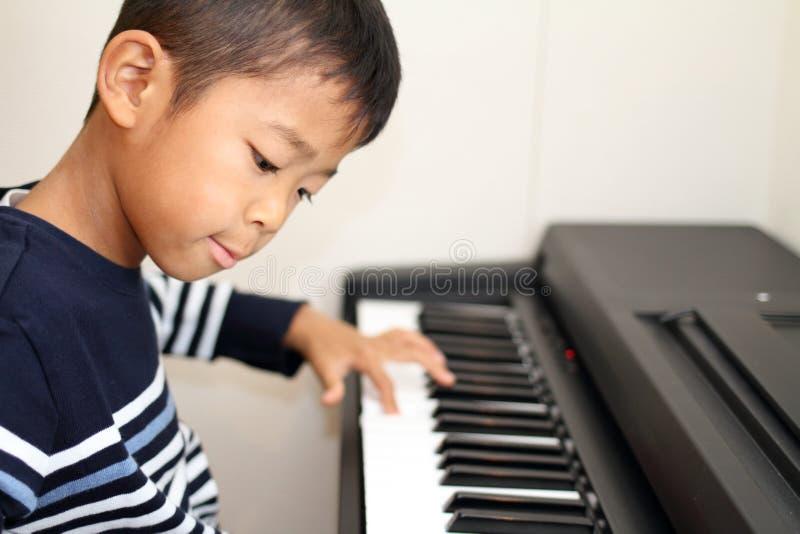 Menino japonês que joga um piano fotos de stock royalty free