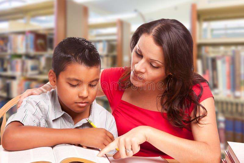 Menino latino-americano e adulto novos de Famle que estuda na biblioteca imagens de stock