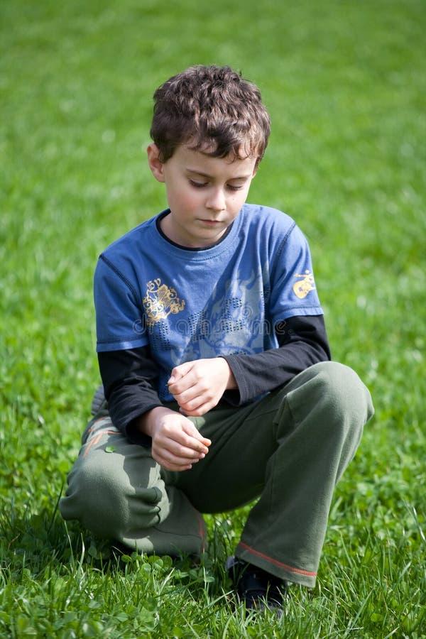 Menino lindo em um campo de grama fotografia de stock royalty free
