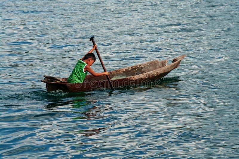 Menino local no barco de pesca, Indonésia. foto de stock