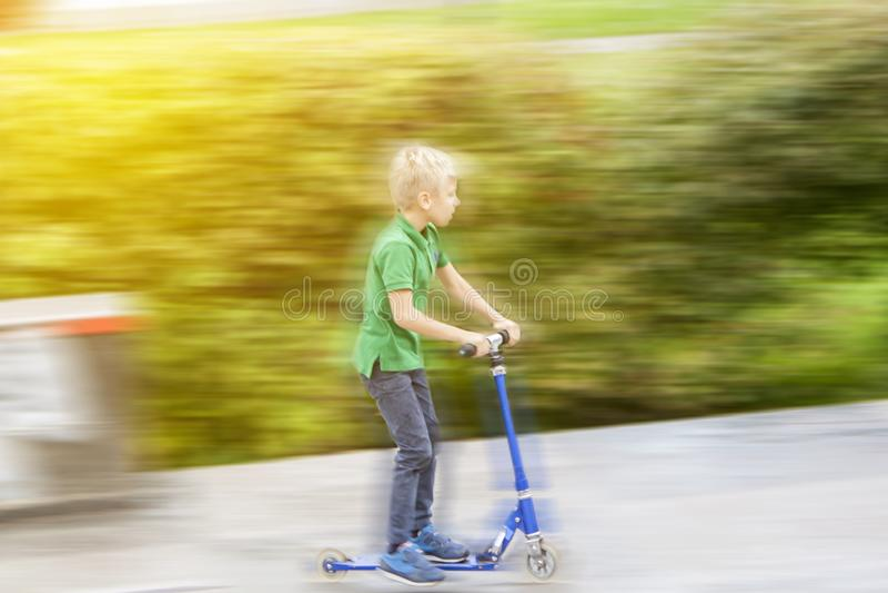 menino loiro em camiseta verde corre em uma scooter no parque foto de stock royalty free