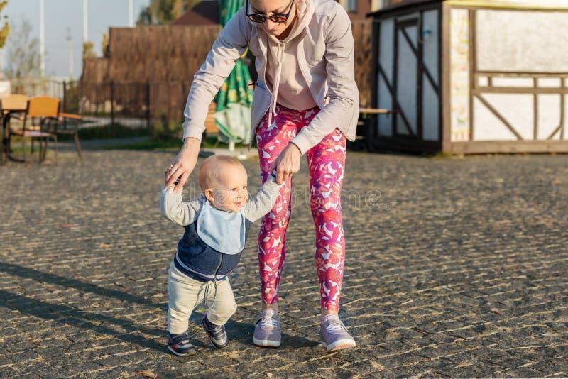 Menino louro adorável pequeno bonito da criança que faz primeiramente etapas com apoio da mãe no parque da cidade em nivelar o te fotos de stock