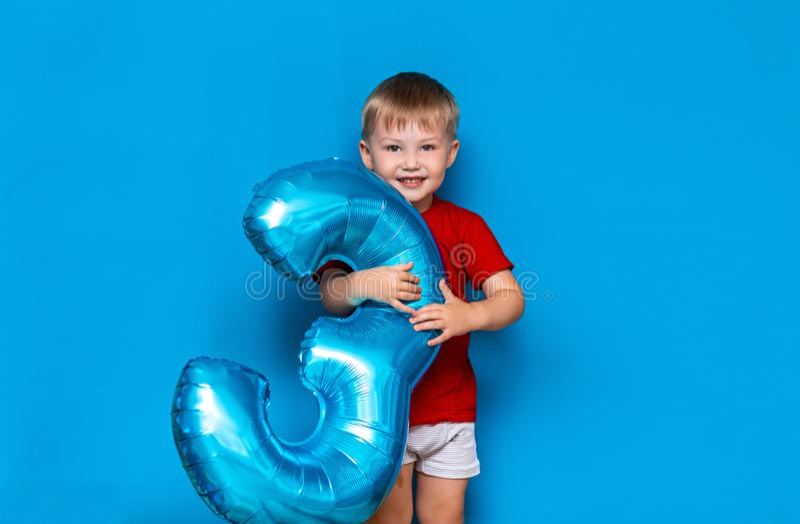 Menino louro bonito pequeno no fundo azul que guarda a cor azul do baloon folha-revestido da esfera feliz aniversario três anos v fotografia de stock