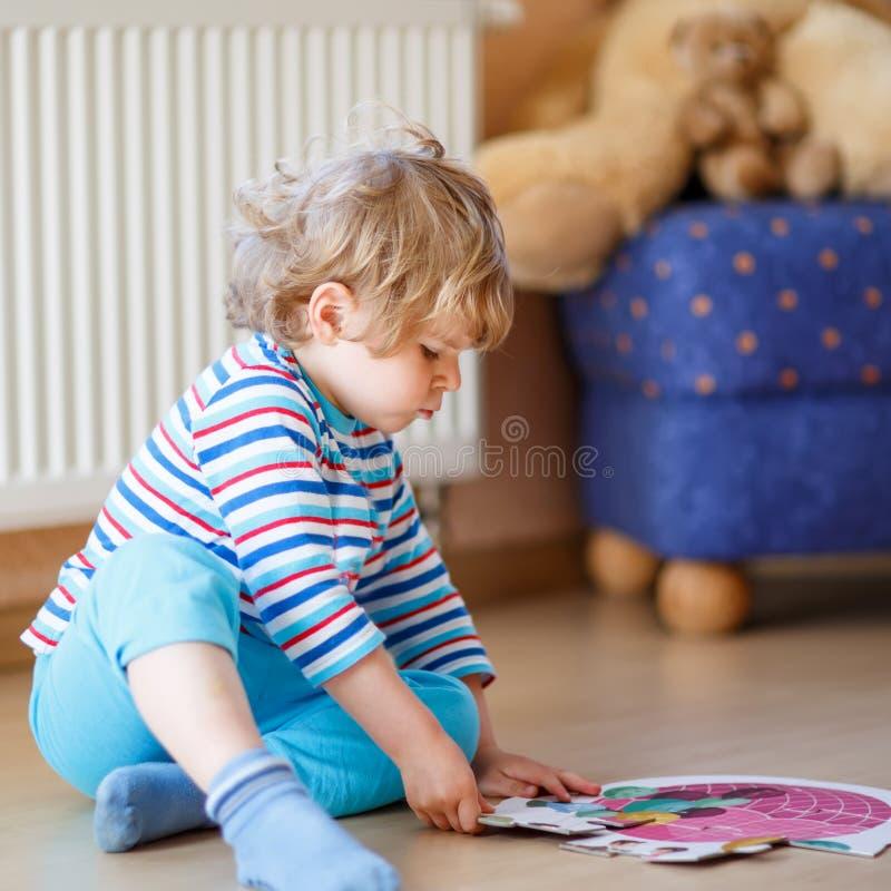 Menino louro bonito pequeno que joga com jogo do enigma em casa fotografia de stock