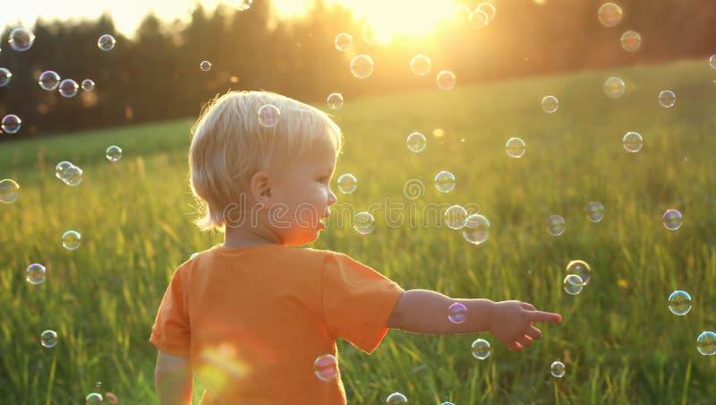 Menino louro da criança bonito que joga com bolhas de sabão no campo do verão Conceito feliz do verão da criança Imagem autêntica imagens de stock