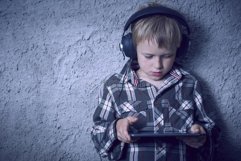 Menino louro da criança que escuta a música ou o filme de observação com fones de ouvido e que usa a tabela digital imagem de stock