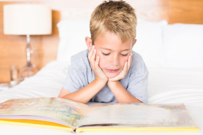 Menino louro feliz que encontra-se na cama que lê um livro de histórias fotos de stock