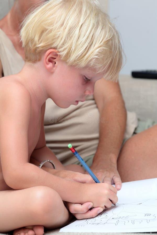Menino louro novo que faz trabalhos de casa com lápis fotos de stock