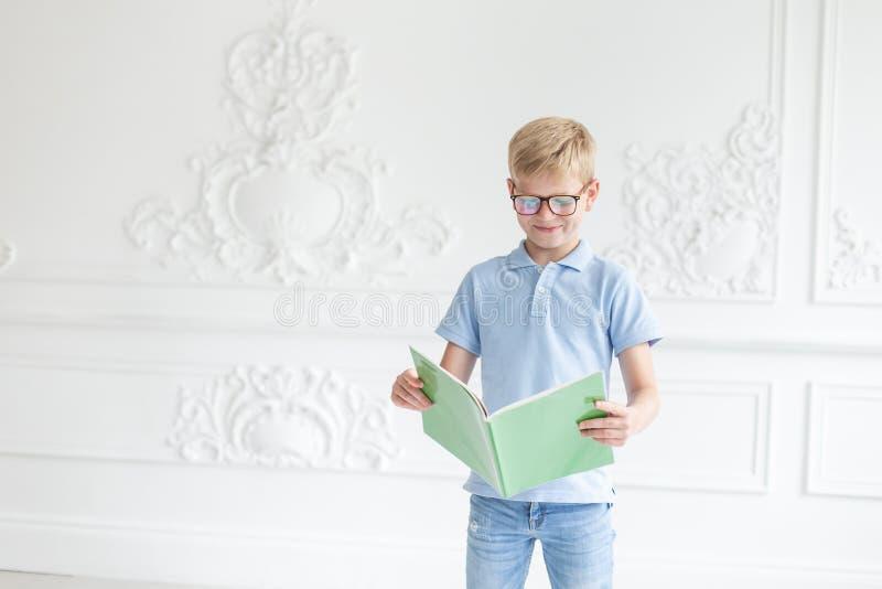 Menino louro novo que levanta em um fundo da parede branca com o livro de texto verde nas mãos imagens de stock royalty free