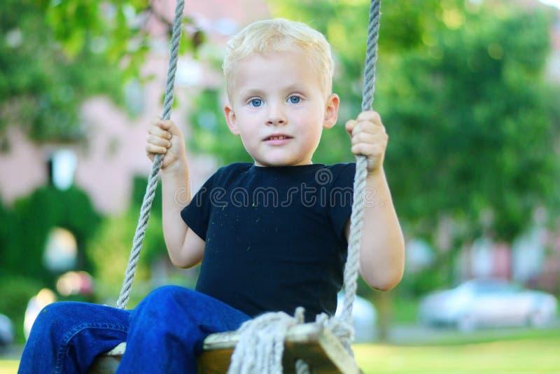 Menino louro pequeno adorável que tem o divertimento no campo de jogos fotos de stock